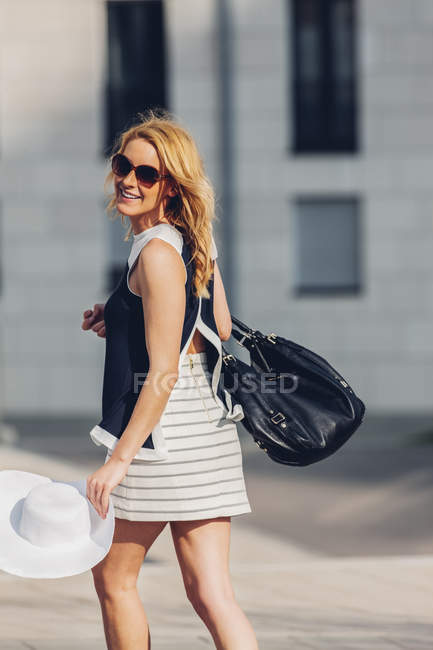 Портрет улыбающейся блондинки в летней шляпе и кожаной сумке в солнечных очках — стоковое фото
