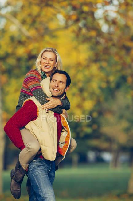 Mann gibt Freundin Huckepack im Herbstpark — Stockfoto