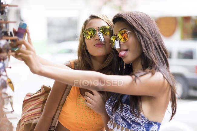 Due giovani donne che provano gli occhiali da sole e si fanno un selfie — Foto stock