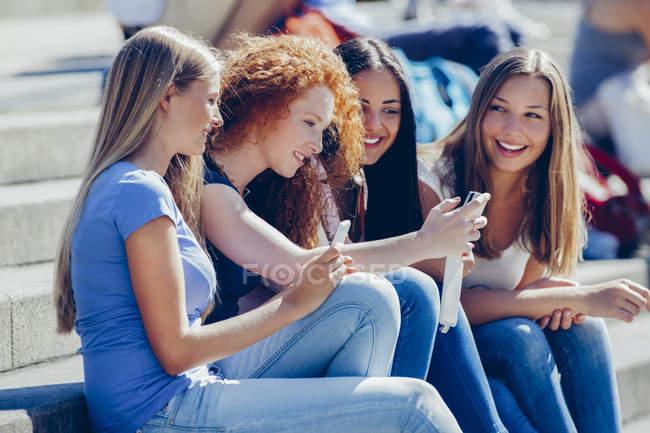 Quatro amigos sentados juntos em passos olhando para o smartphone — Fotografia de Stock