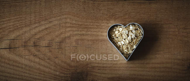Rolled oats in a heart-shaped cookie cutter on wood — Stock Photo