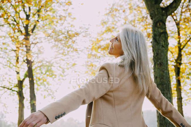 Woman enjoying day at autumnal park — Stock Photo