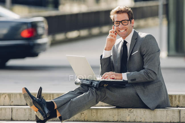 Businessman sitting on steps and using laptop — Stock Photo