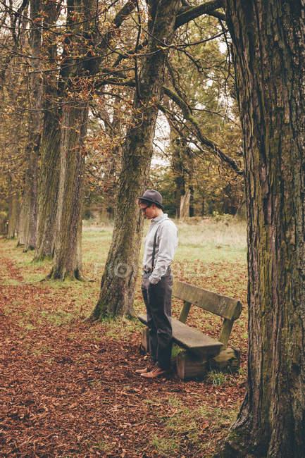 Giovane uomo in piedi davanti a una panchina nel parco autunnale — Foto stock