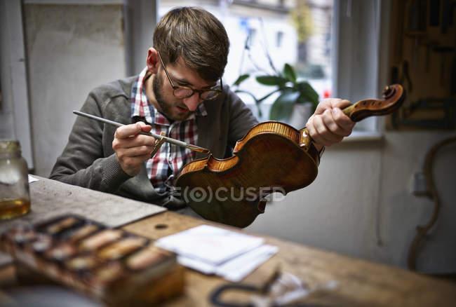 Geigenbauer in seiner Werkstatt Lackierung repariert Violine — Stockfoto
