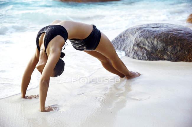 Seychelles, woman bridge position at seafront — Stock Photo