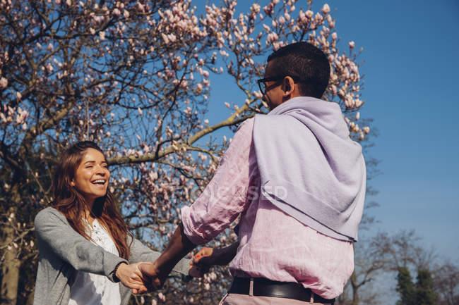 Щасливі молода пара холдингу руки в парку — стокове фото