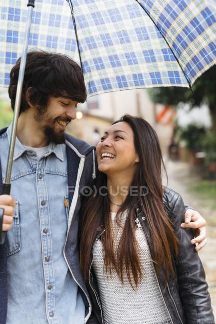 Heureux jeune couple avec parapluie — Photo de stock