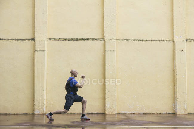 Man doing proper lunge exercise in front of a wall — Stock Photo