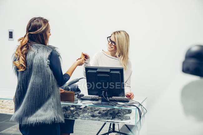 Woman paying at store counter in a boutique — Stock Photo