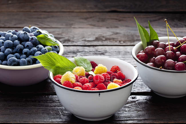 Bowls of sour cherries and blueberries — Stock Photo