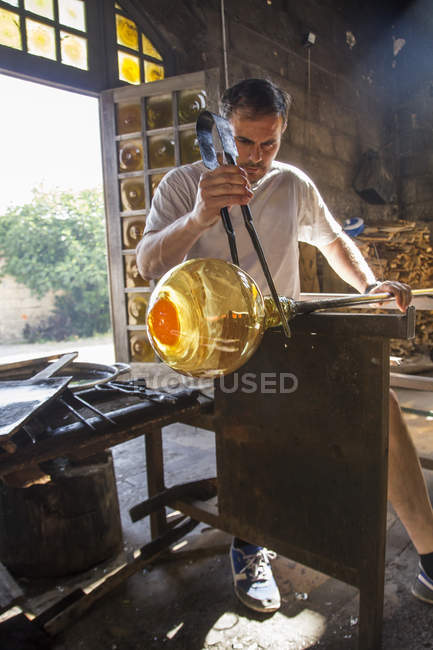 Man working with molten glass using a tweezers in a glass factory — Stock Photo