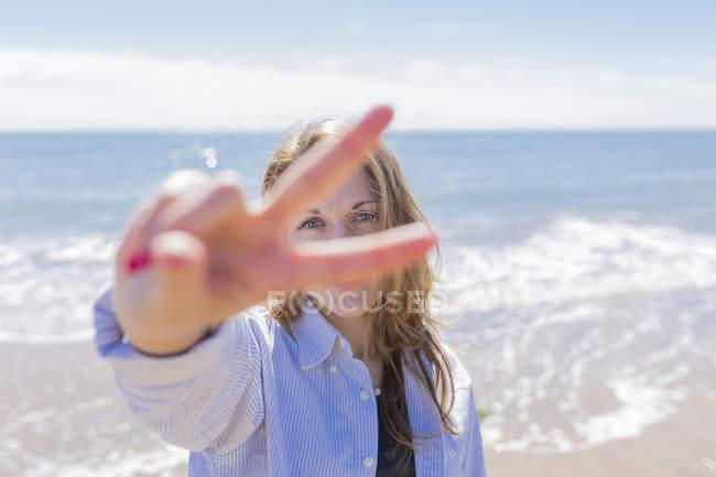 Portrait de jeune femme regardant à travers ses doigts montrant le signe de la victoire — Photo de stock