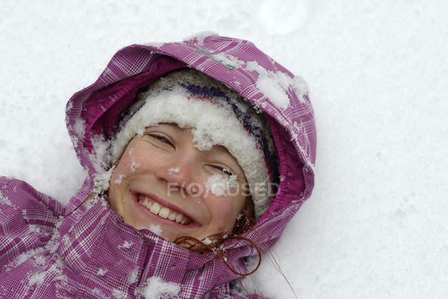 Ritratto di ragazza sorridente sdraiata sulla neve — Foto stock