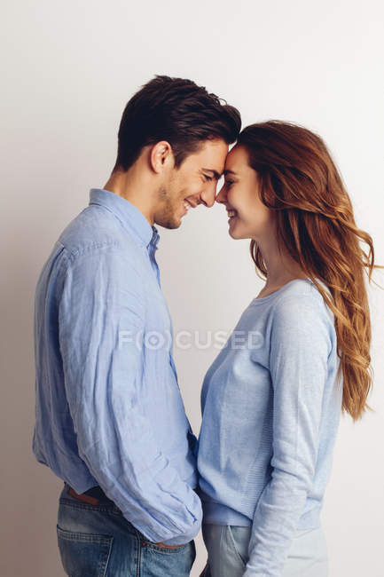 Happy young couple standing face to face in front of white background — Stock Photo
