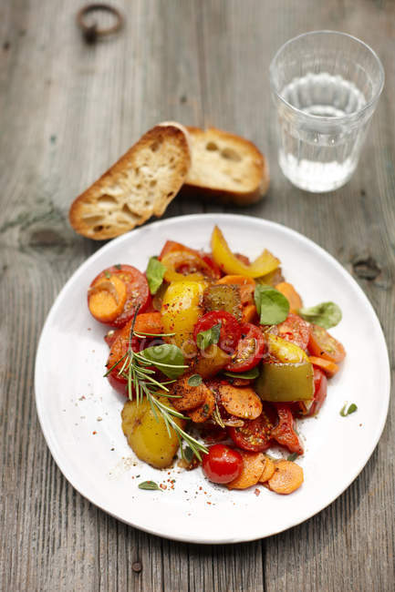 Plate of vegan antipasti, slices of ciabatta and glass of water — Stock Photo