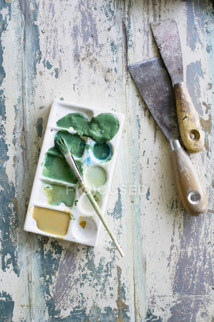 Spatulas, paint brush and artist's palette on painted wood — Stock Photo