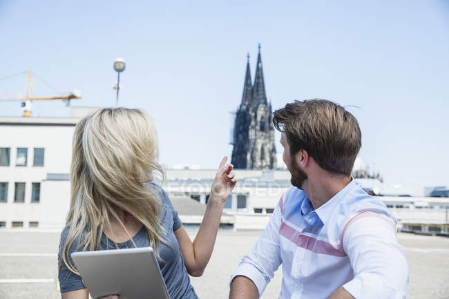 Germany, Cologne, young couple with digital tablet looking at Cologne Cathedral — Stock Photo