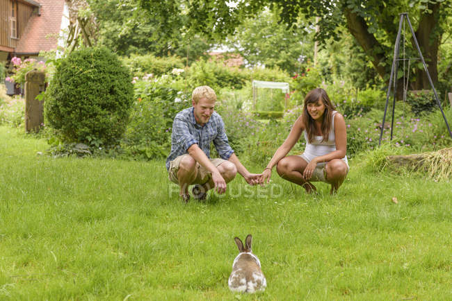 Young couple expecting baby, crouching in garden, watching bunny — Stock Photo