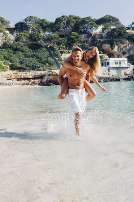 Man piggybacking girlfriend — Stock Photo