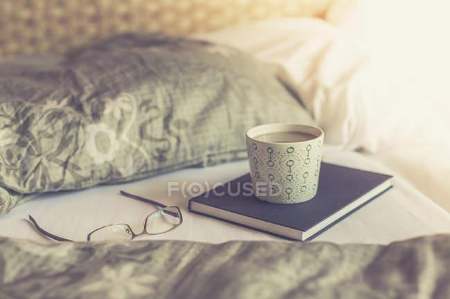 Книга, читання окуляри і білий кави на ліжку — стокове фото
