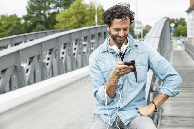Усміхнений чоловік на мосту, дивлячись на мобільний телефон — стокове фото
