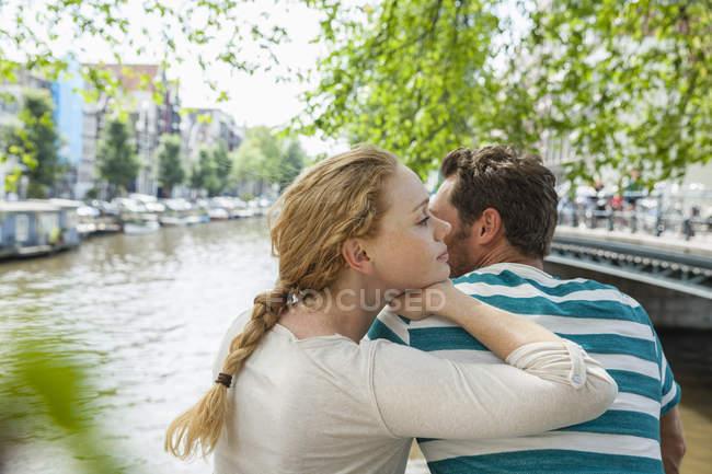 Нидерланды, Амстердам, расслабленная пара на городском канале — стоковое фото