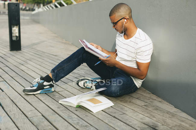 Student sitting with booklets — Stock Photo
