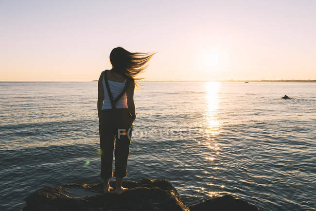 France, Pornichet, woman with blowing hair standing at seafront watching sunset — Stock Photo