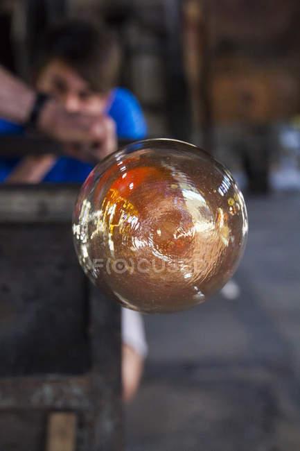Homem soprando vidro fundido com um tubo em uma fábrica — Fotografia de Stock