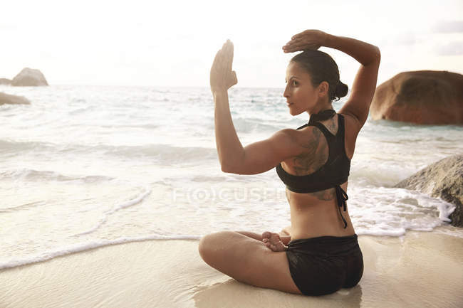 Seychelles, woman doing yoga exercise at seafront — Stock Photo
