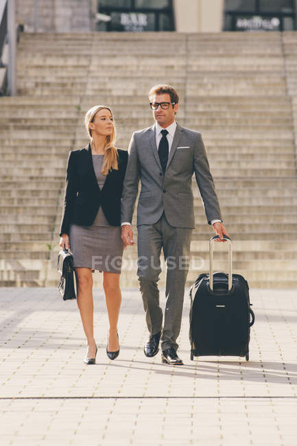 Businessman and businesswoman walking together with suitcase — Stock Photo
