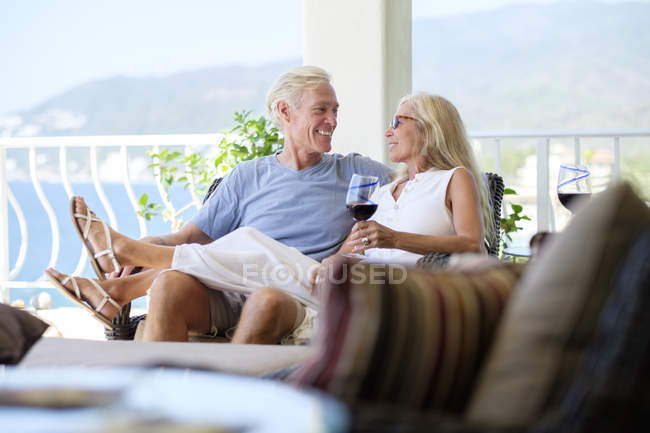 Happy senior couple with glass of red wine in home by the sea — Stock Photo