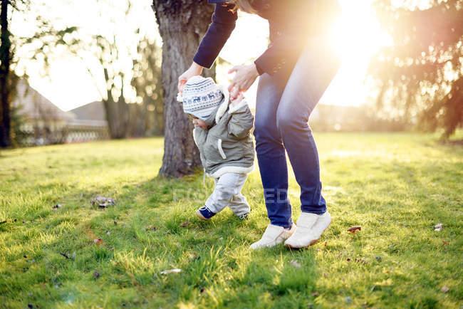 Babymädchen auf einer Wiese mit Hilfe der Mutter laufen lernen — Stockfoto