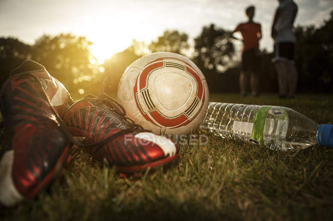Fußballschuhe, Ball und Wasserflasche auf dem Fußballplatz — Stockfoto
