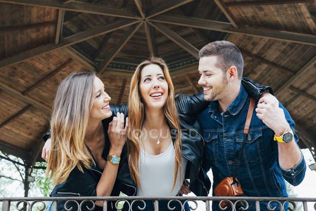 Три счастливых друга обнимаются на открытом воздухе — стоковое фото