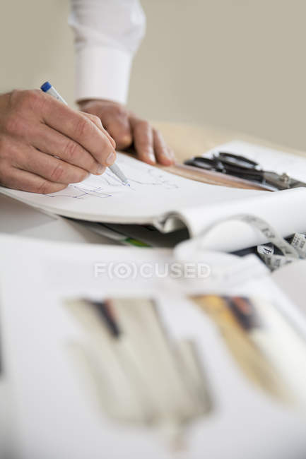 Tailor drawing cut pattern — Stock Photo