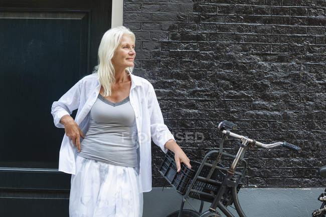 Mujer senior de Holanda, Amsterdam, de pie con la bici delante de casa - foto de stock