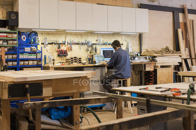 Carpenter working with computer in workshop — Stock Photo