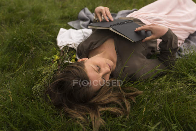Женщина отдыхает на лугу с книгой — стоковое фото