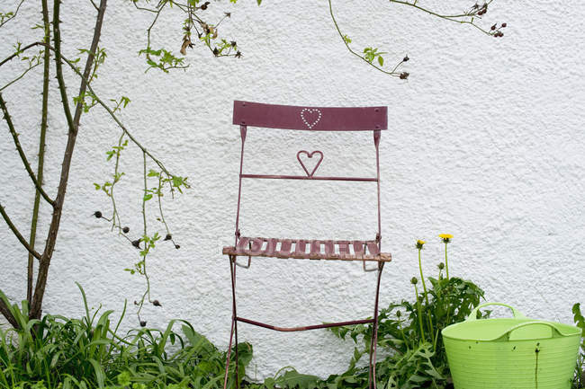 Garden chair in front of a wall outdoors — Stock Photo