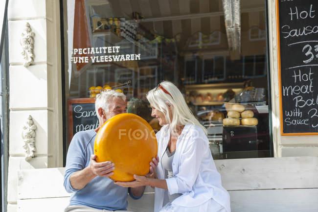 Нидерланды, Амстердам, пожилая пара сидит на скамейке с буханкой сыра — стоковое фото