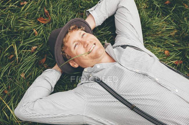 Портрет улыбающегося молодого человека, лежащего на лугу с руками за головой — стоковое фото