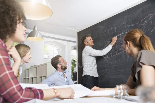 Chers collègues dans le bureau moderne ayant une réunion — Photo de stock