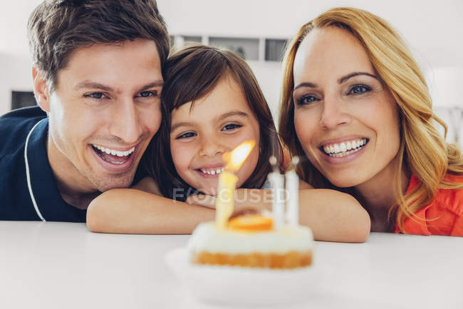 Family with daughter celebrating birthday with candles on cake — Stock Photo