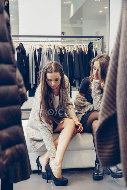 Two young women shopping for shoes in a boutique — Stock Photo