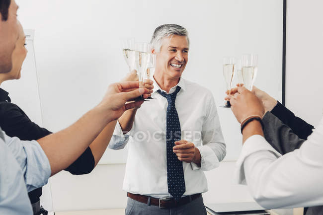 Group of business people raising  toast with champagne in office — Stock Photo