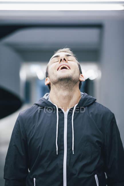 Porträt des Mannes mit Kopf zurück trägt schwarze Kapuzenjacke — Stockfoto