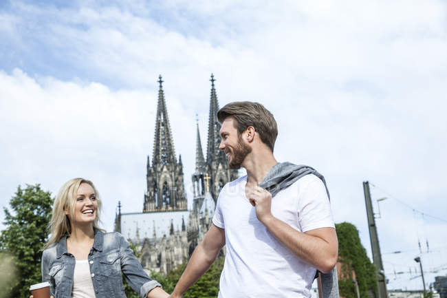 Germany, Cologne, happy young walking hand in hand — Stock Photo