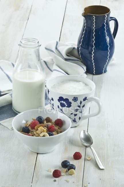 Сніданок з мюслі та фруктами, капучіно і пляшка молока — стокове фото